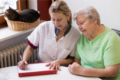 caregiver and senior woman writing on the notebook