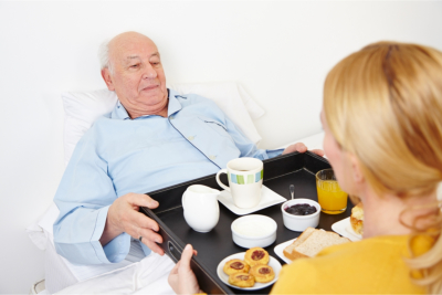 caregiver giving food to the senior man